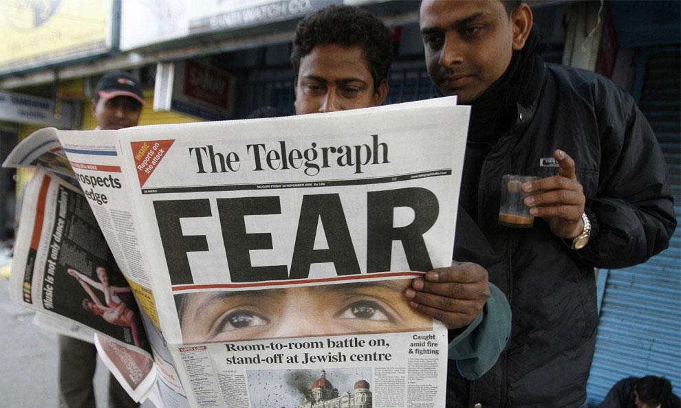 Люди читают газету о террористическом акте, Индия, фото