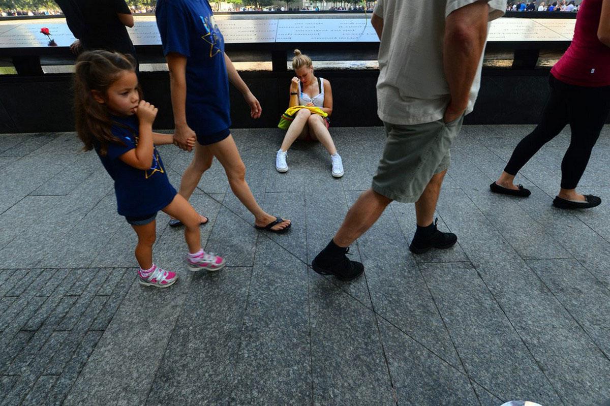 девушка сидит у Мемориала 9/11 в Нью-Йорке