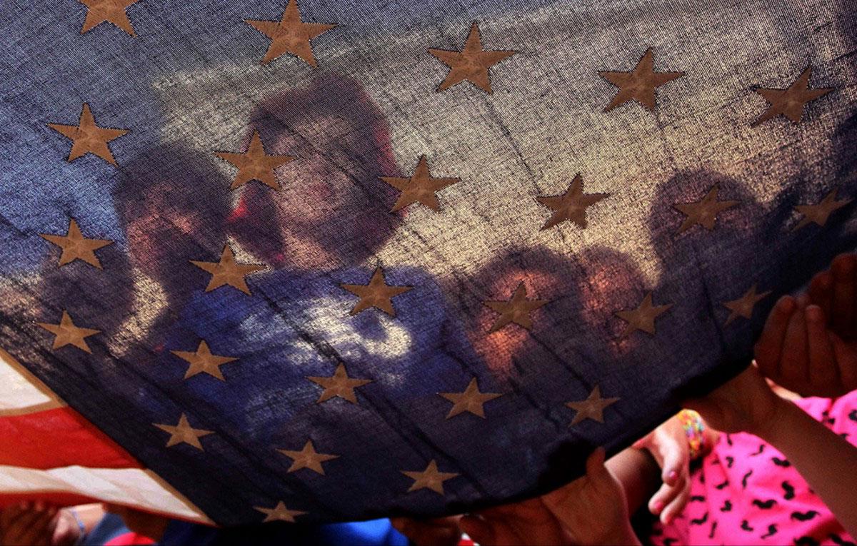 люди поднимают американский флаг