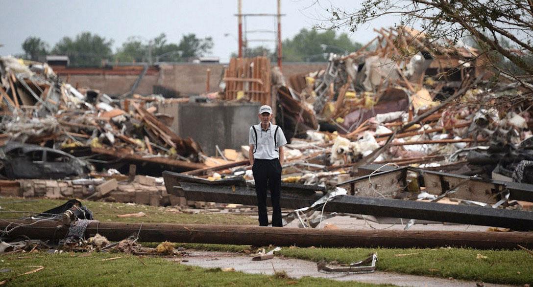 мужчина на руинах своего дома