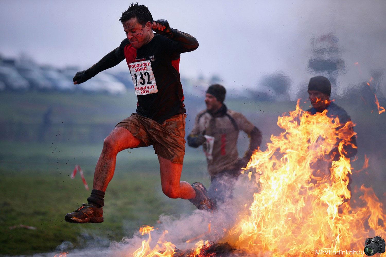 Спортсмены прыгает через горящее сено