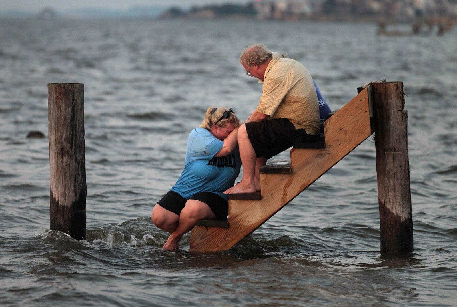 люди на ступеньках смытого ураганом дома