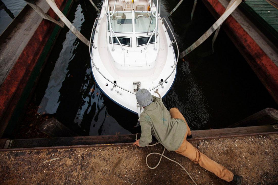 работник крепит лодку, фото из Нью-Йорка