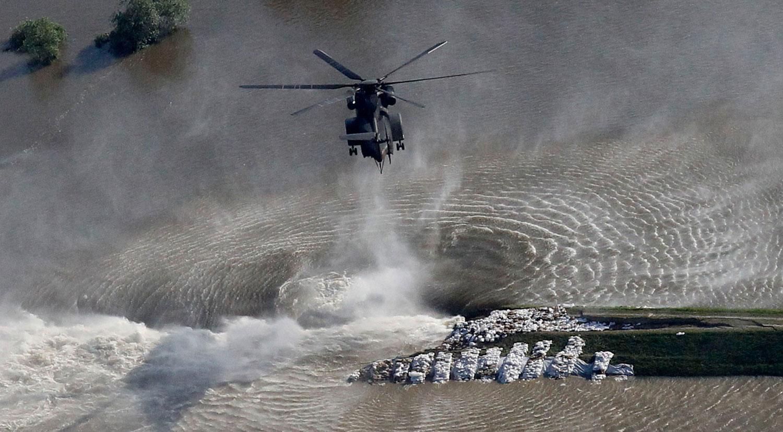 Вертолет сбрасывает мешки с песком