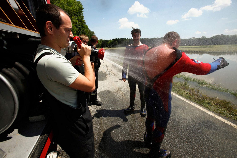Пожарник поливает водой людей