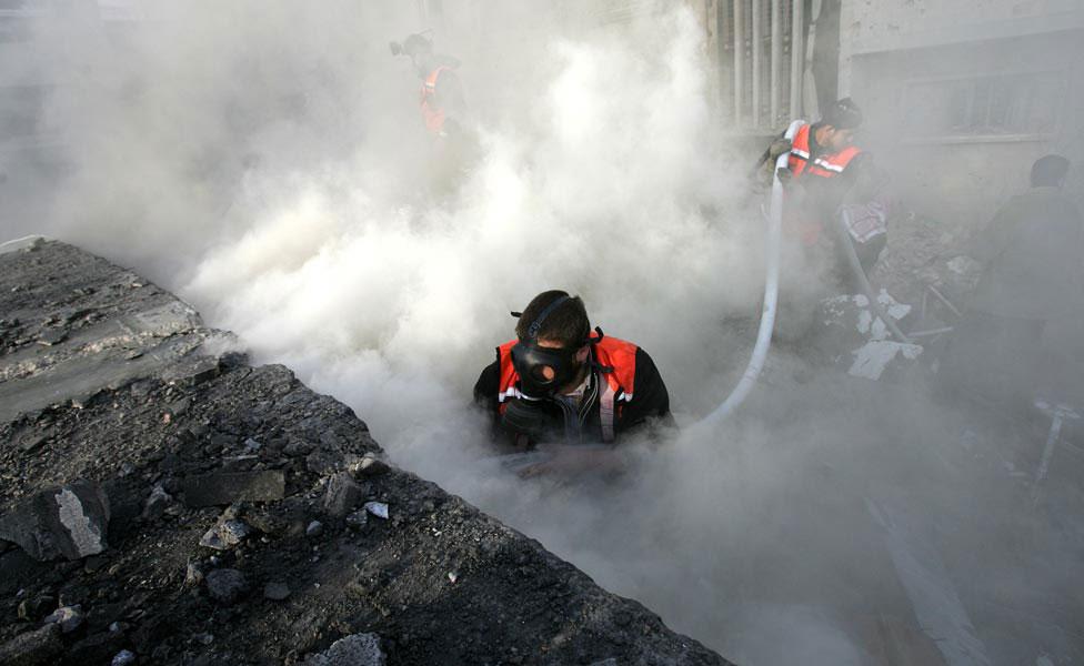 Палестинские пожарные среди обломков разрушенного здания, фото