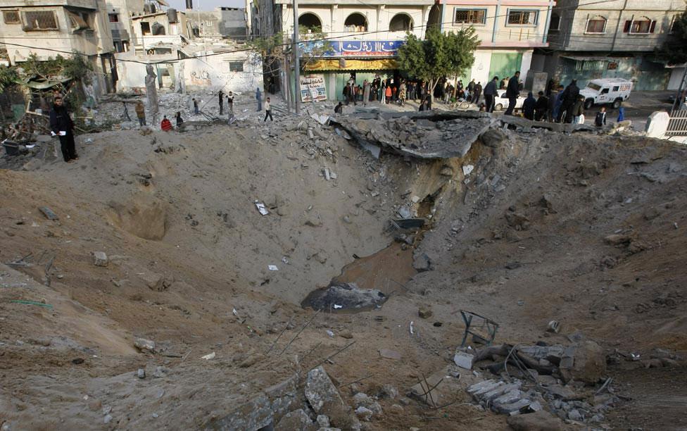 Палестинцы осматривают кратер от бомбы, фото