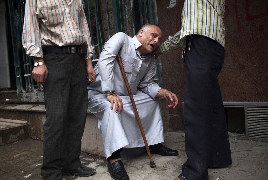 Мужчина у морга скорбит по убитому сыну, фото, война