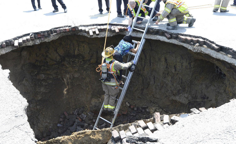 женщине помогают выбраться из ямы