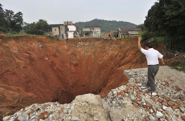 мужчина бросает камень в воронку