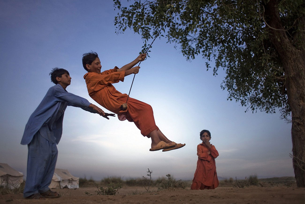 пакистанские дети катаются на самодельных качелях
