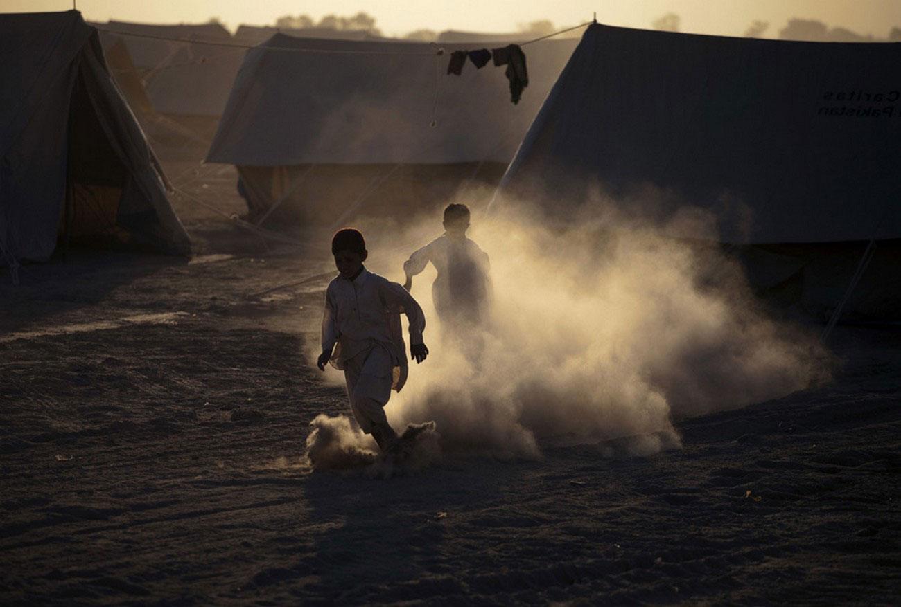 мальчишки носятся в пыли Пакистана