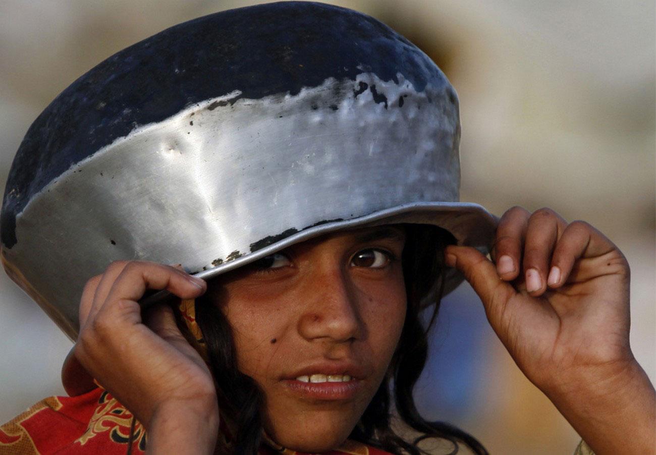 девочка-беженка в кастрюлей