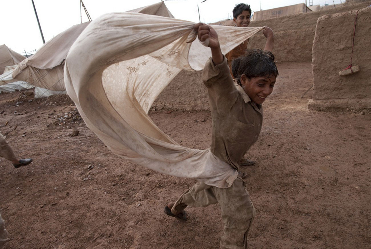 ребенок с простыней в лагере вынужденных переселенцев