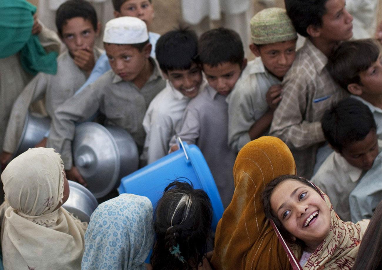 пакистанцы в очереди за едой в лагере вынужденных перселенцев