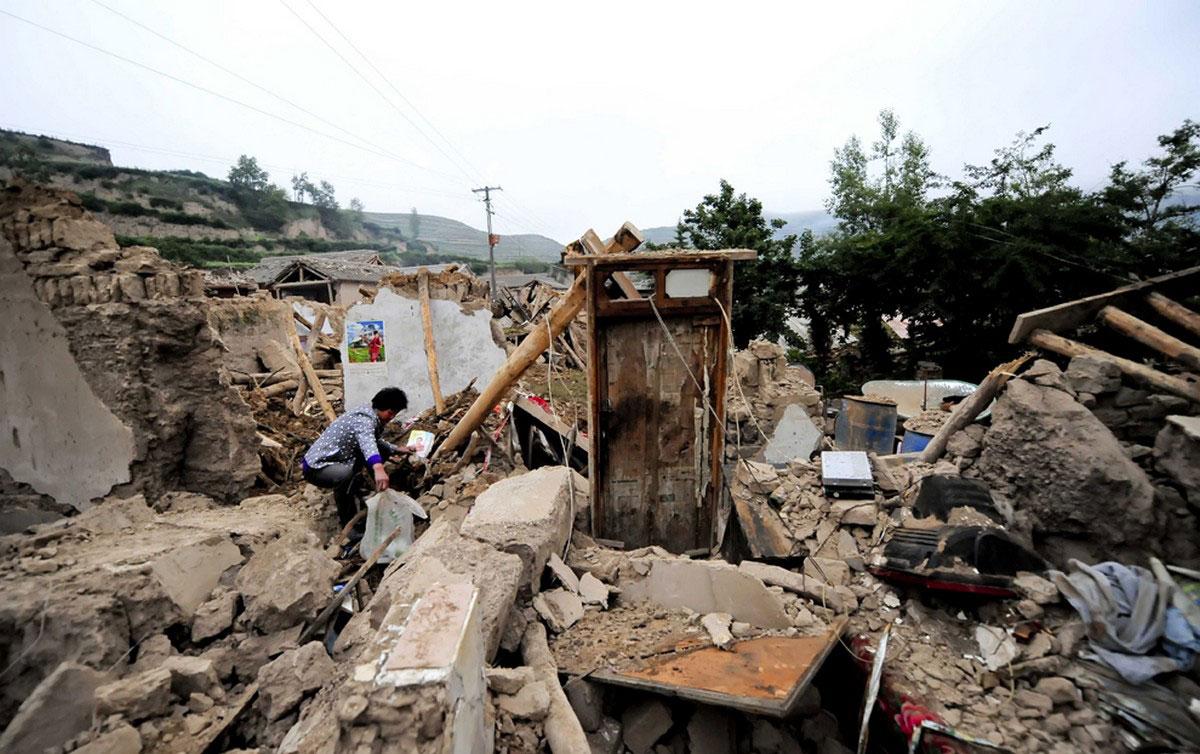 Женщина на руинах своего дома
