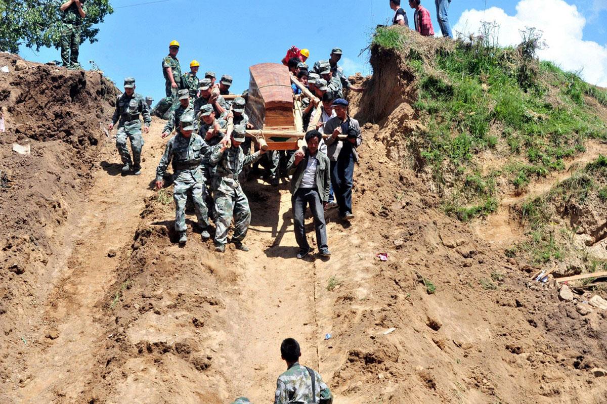 Спасатели несут гроб
