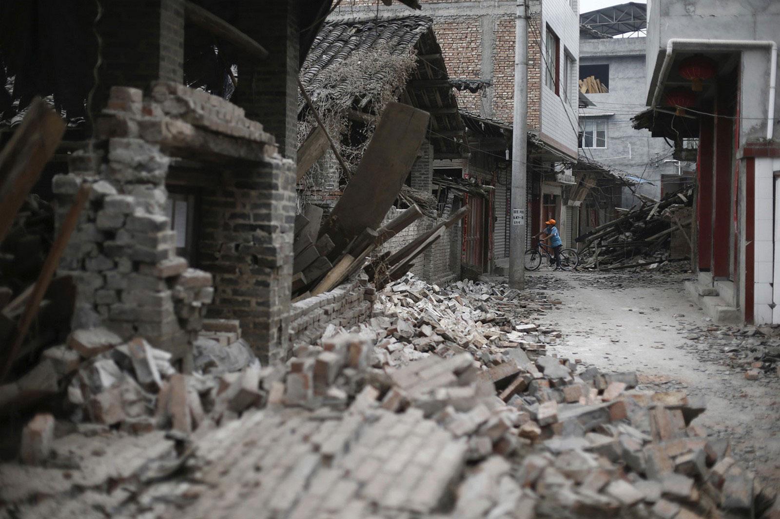 Мальчик на велосипеде среди разрушенных домов