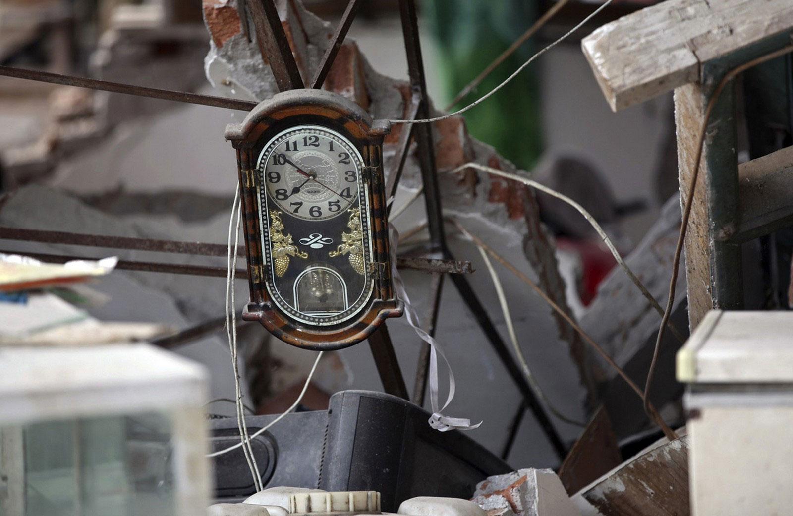 Часы среди обломков здания