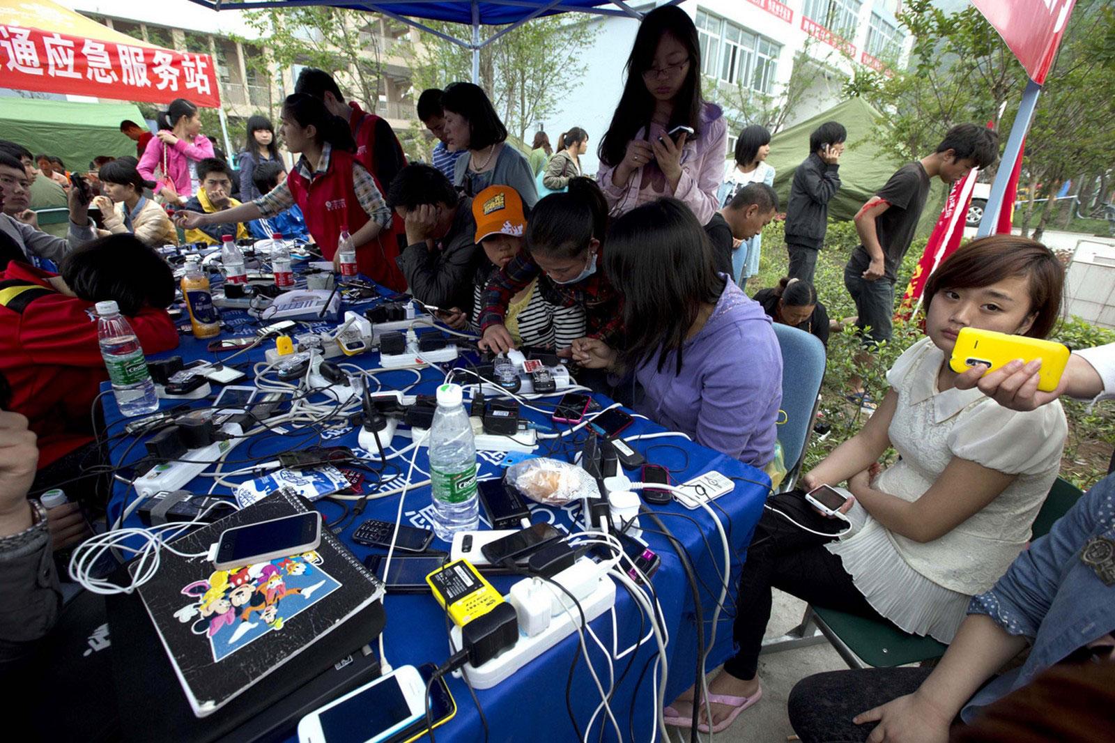 Люди заряжают свои мобильные телефоны