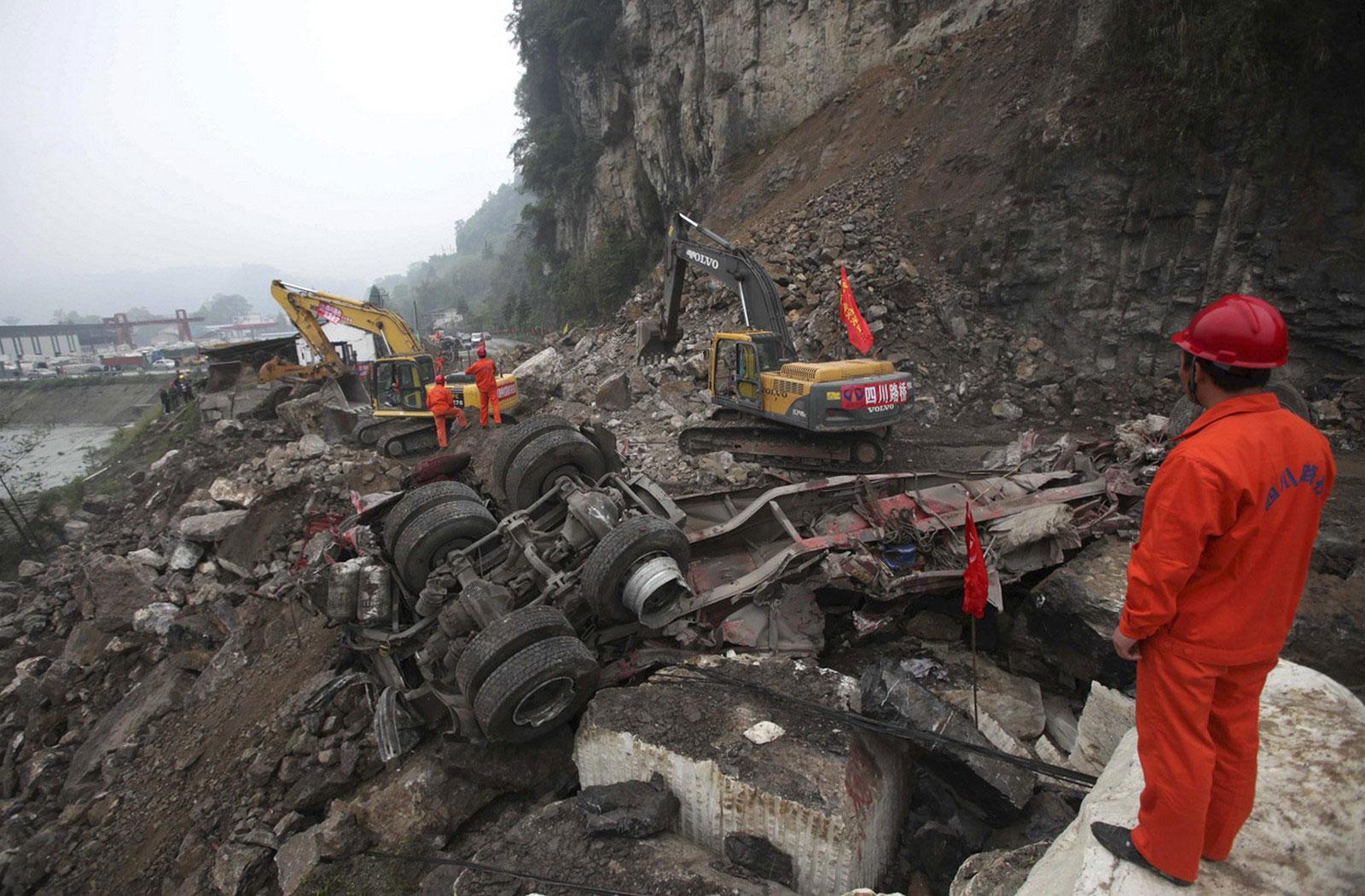 Экскаваторы расчищают дорогу после оползня в Китае
