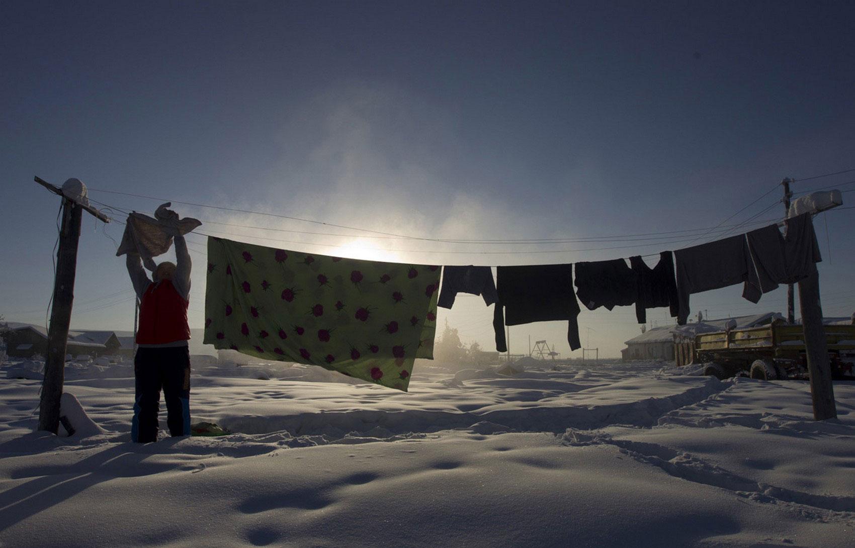 женщина вешает сушиться белье