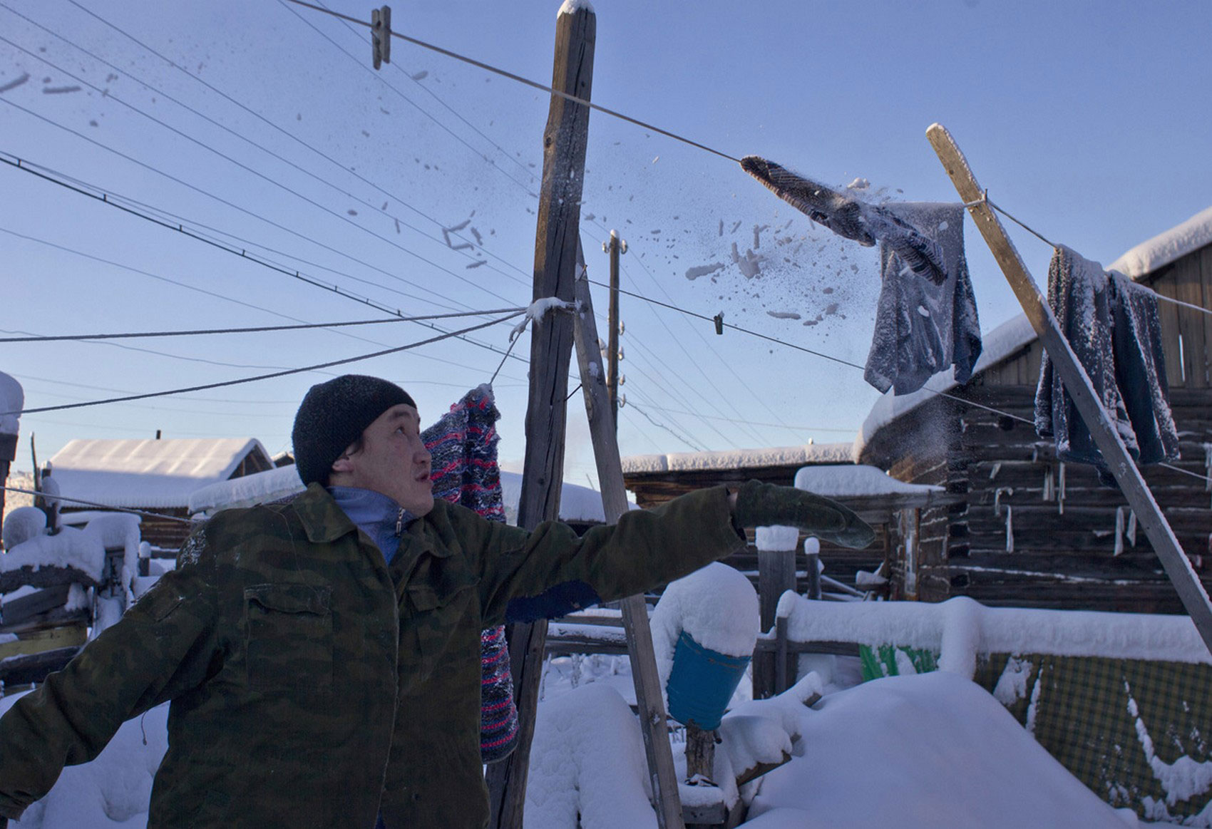 мужчина счищает снег с замерзшего белья